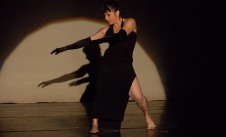 Woman dressed in black dancing on stage