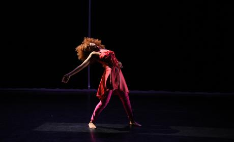 Dancer silhouetted on stage with arms outstretched