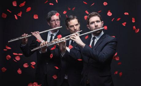 Three men playing flutes with roses falling around them
