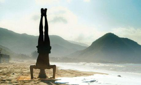 Man in silhouette doing a handstand on a beach