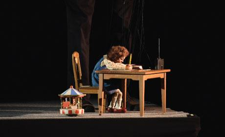 Girl puppet hunched over a desk writing