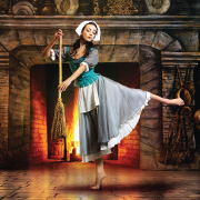 Dancer dressed as Cinderella holding broom