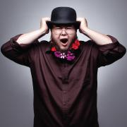Artist Shane Koyczan grasping at his hat with both hands.