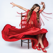 Female flamenco dancer sitting in red dress