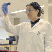 Female scientist holding up a specimen for examination