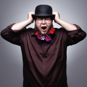 Artist Shane Koyczan grasping at his hat with both hands.